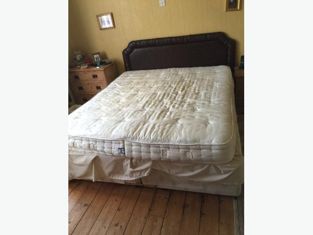 kingsize bed and mattress with brown leather headboard