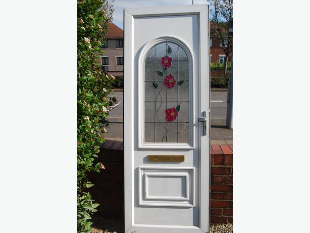 front upvc door with leaded coloured glass rose motif.