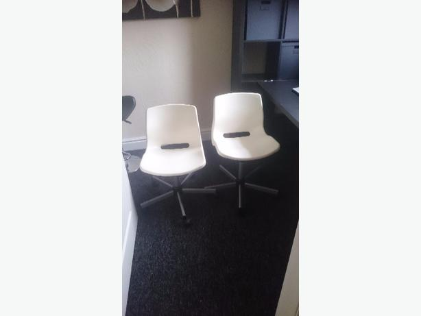 two white plastic office computer chairs