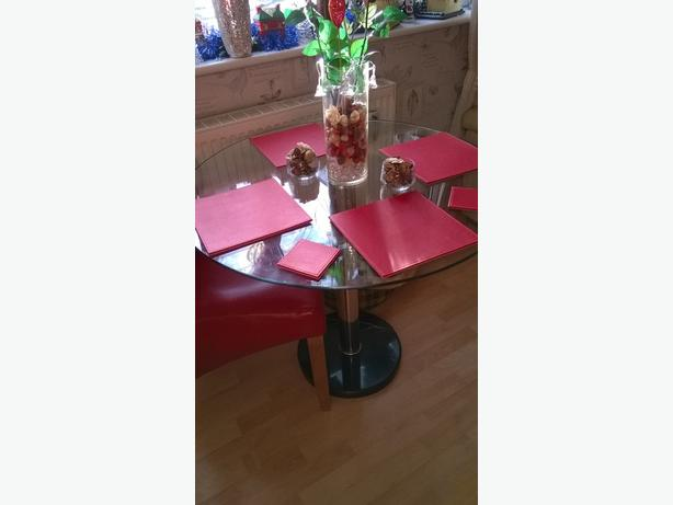 round solid glass table and one red chair