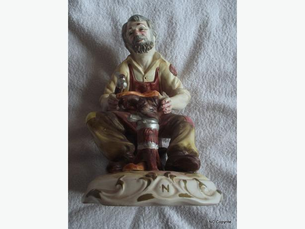 LARGE CAPODIMONTE FIGURINE OF A COBBLER ON TREE STUMP (DAMAGE ON BASE)