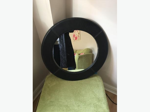 brown round leather mirror and magazine rack