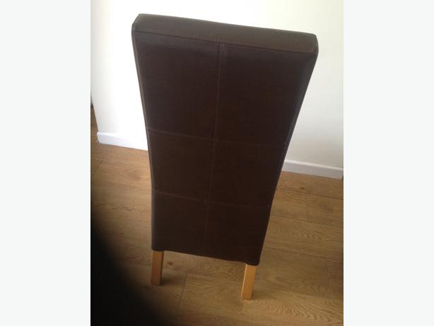 Two dark brown faux leather dining chairs.