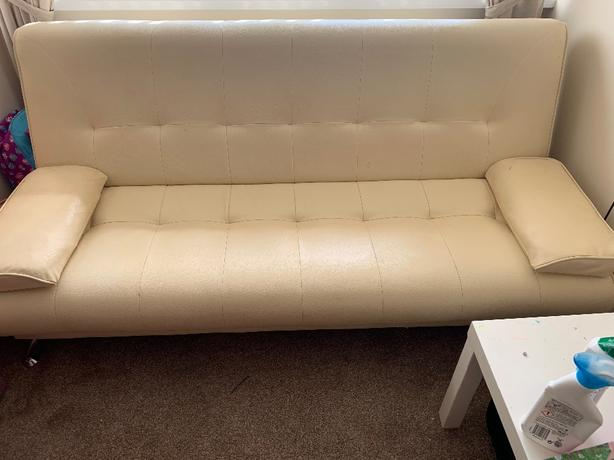 Cream faux leather click/clak sofa bed.