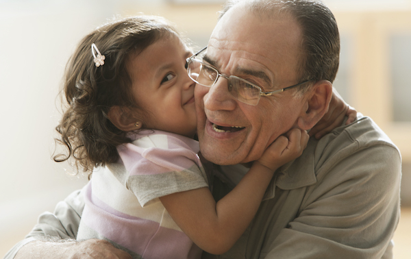 Little girl hugging her grandfather.