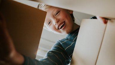 Happy boy playing with a box - Pediatric Blood Disorders