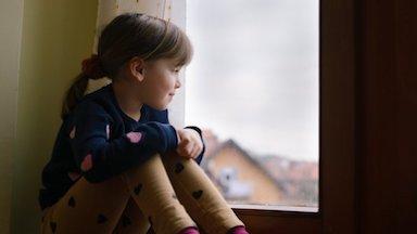 Child looking outside through a window - Pediatric Neurology