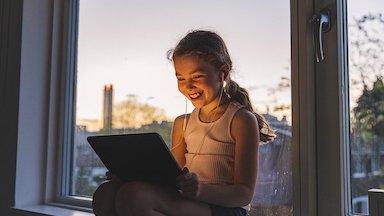 Girl reading a book by a window - Pediatric Pulmonary
