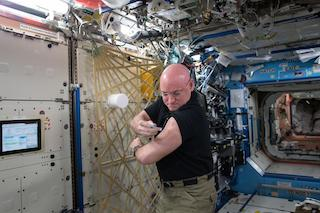Astronaut Scott Kelly gives himself a flu shot during his yearlong mission to the International Space Station