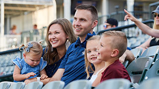 Burchett family sitting in the stands at the Frisco baseball stadium.