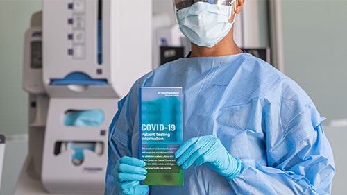 Doctor holding a COVID-19 patient testing pamphlet