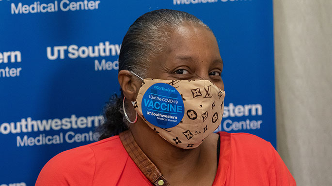 Older African American woman with a face mask and COVID-19 Vaccination I Got the Shot sticker.
