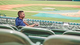Scott Burchett sitting in the stands of the Frisco baseball stadium.