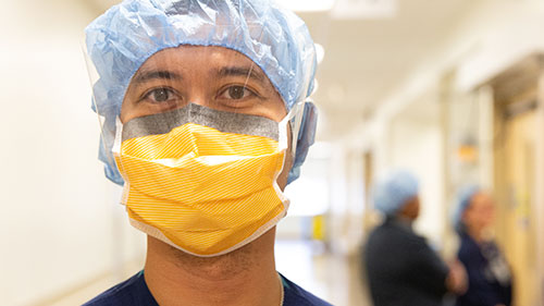Male nurse wearing a bright yellow face mask and PPE