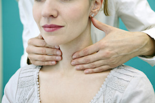 woman getting her thyroid examined