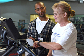 Marcel Turner  watches as Tammy Lewis tests an exercise program