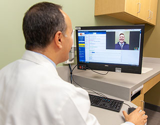 Virtual care visit with a doctor talking to a patient on the computer