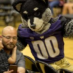 Harry the Husky mascot talks to small child and father