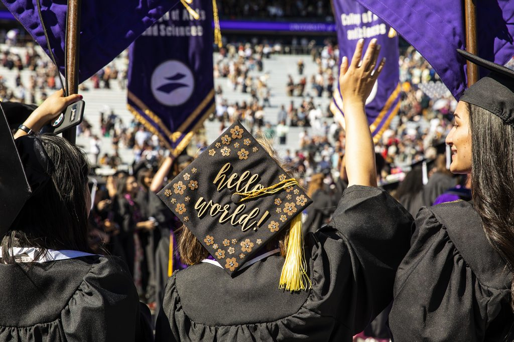 Photo of graduates in caps and gowns from the back. On June 15, 2019, the University of Washington honored more than 6,000 graduates in the 144th Annual Commencement Exercises at Husky Stadium. Nearly 13,795 UW degrees were conferred at the Seattle campus in June. (Photo by Mark Stone)