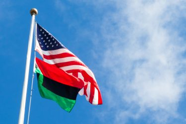The Pan-African flag flies beneath the American flag