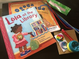 Two children's books: Lola at the Library by Anna McQuinn, and Oonga Boonga by Frieda Wishinsky. Playdough, stickers, blank journal, bubbles, kaledoscope, and pipecleanears.