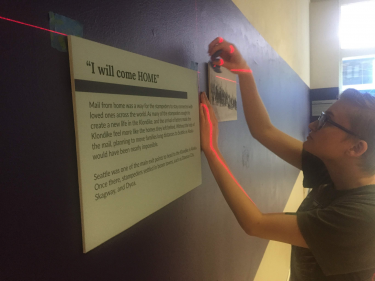 Gabrielle Friesen leveling out labels on the walls of the Kerr Room at the Klondike.