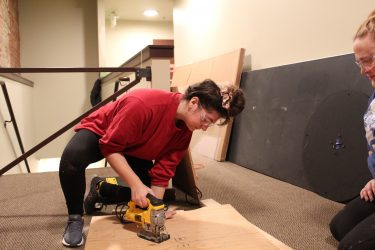 Student cutting exhibit materials at Klondike Gold Rush National Historical Museum.