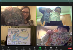 Picture of students and Dylan holding up their craft beeswax wraps.