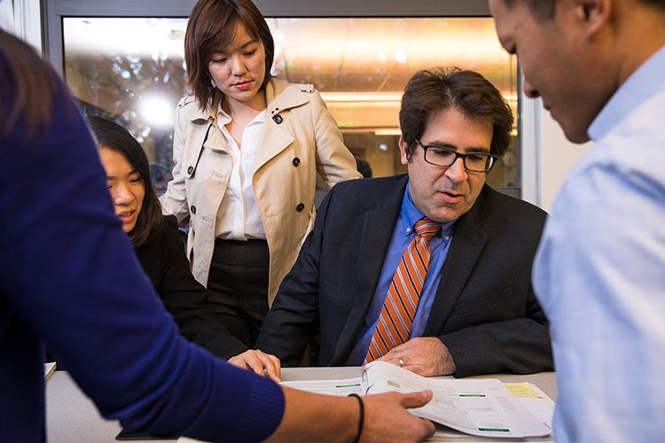 People in business attire analyze documents at a table.
