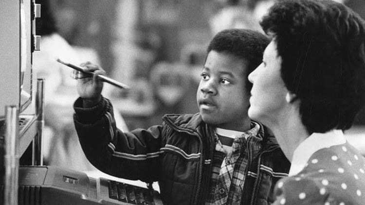 African American boy pointing_at_computer_monitor Helping One Student to Succeed HOSTS Corporation Vancouver Washington 1985