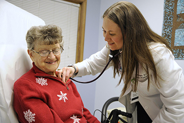 female doctor pressing stethoscope onto chest of elderly woman