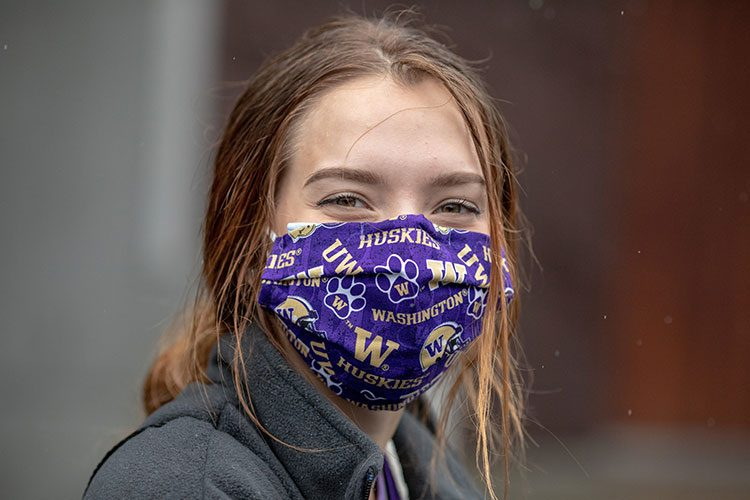 Person wearing UW-branded face mask