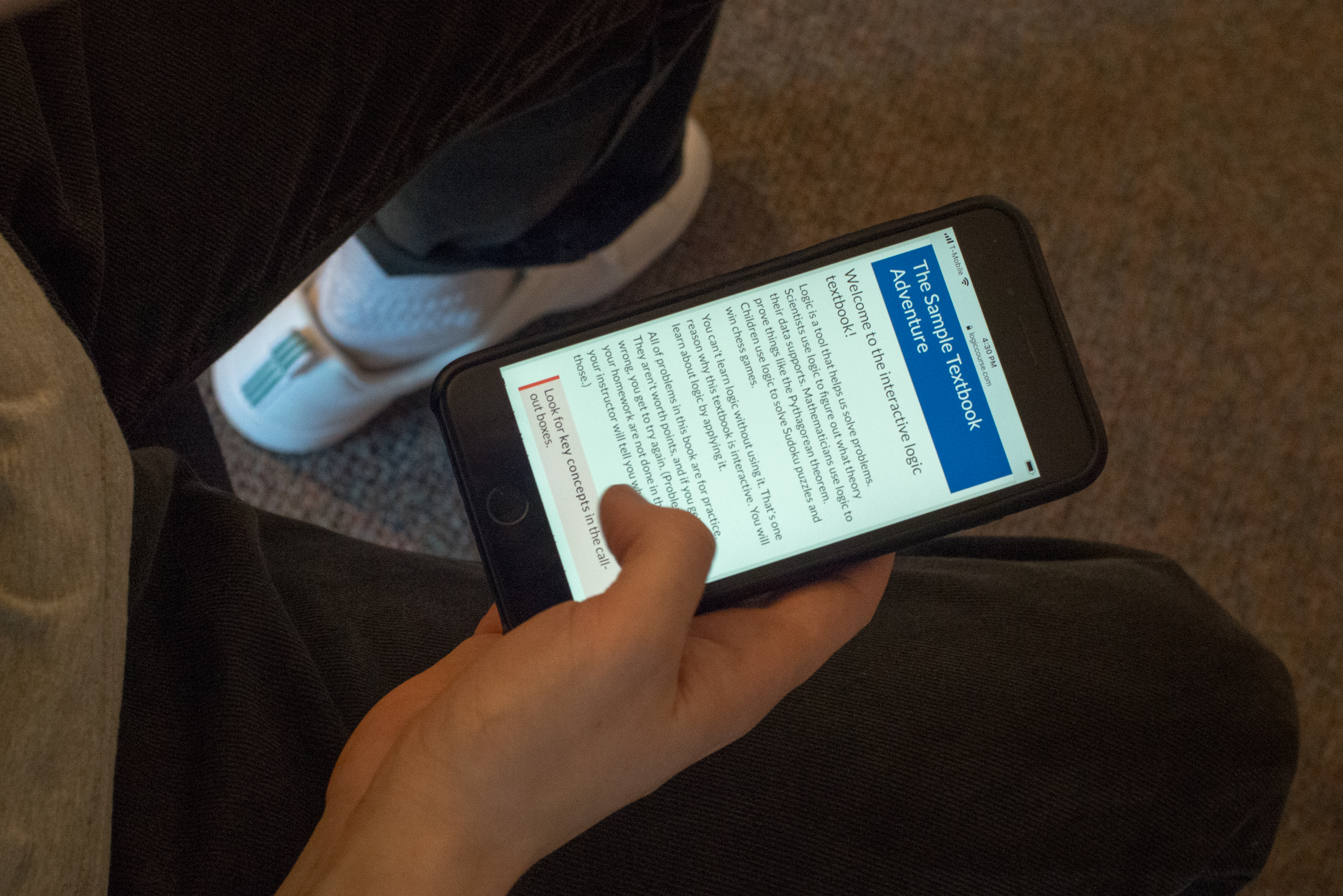 student reading textbook on their phone picture