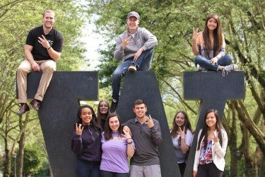 Students pose for a picture at the W Statue at the north entrance of campus.