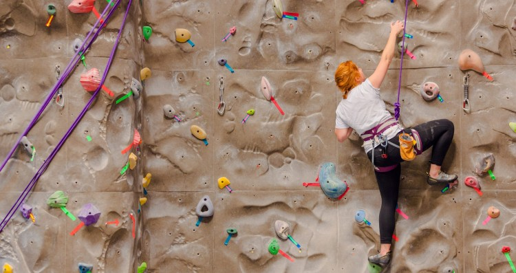 Student using the indoor rock wall at the UW IMA