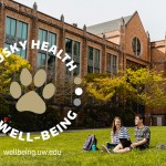 Two students sitting and talking on the HUB lawn
