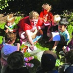 Adult sitting in grass with group of preschool aged youth