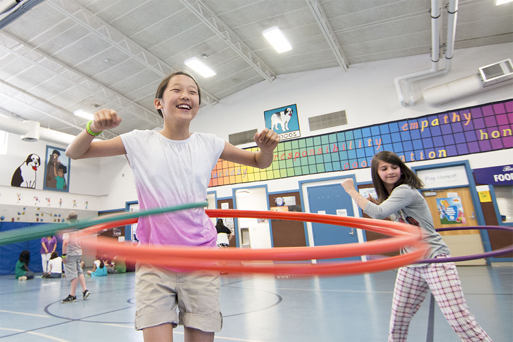 Two school aged children using hula hoops in a gym with group of children in the background