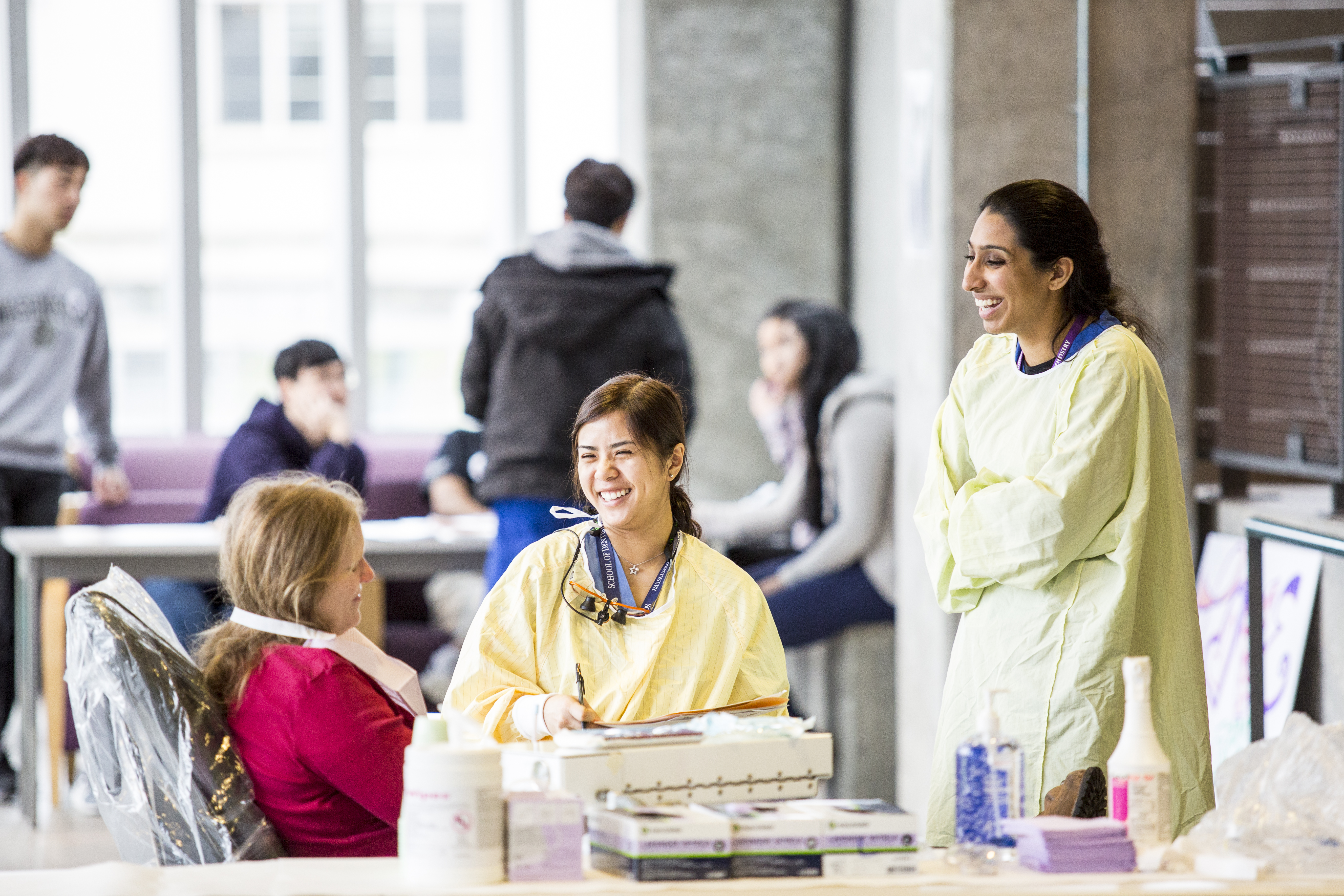 Two dentistry students care for a patient during a Husky Health Bridge clinic