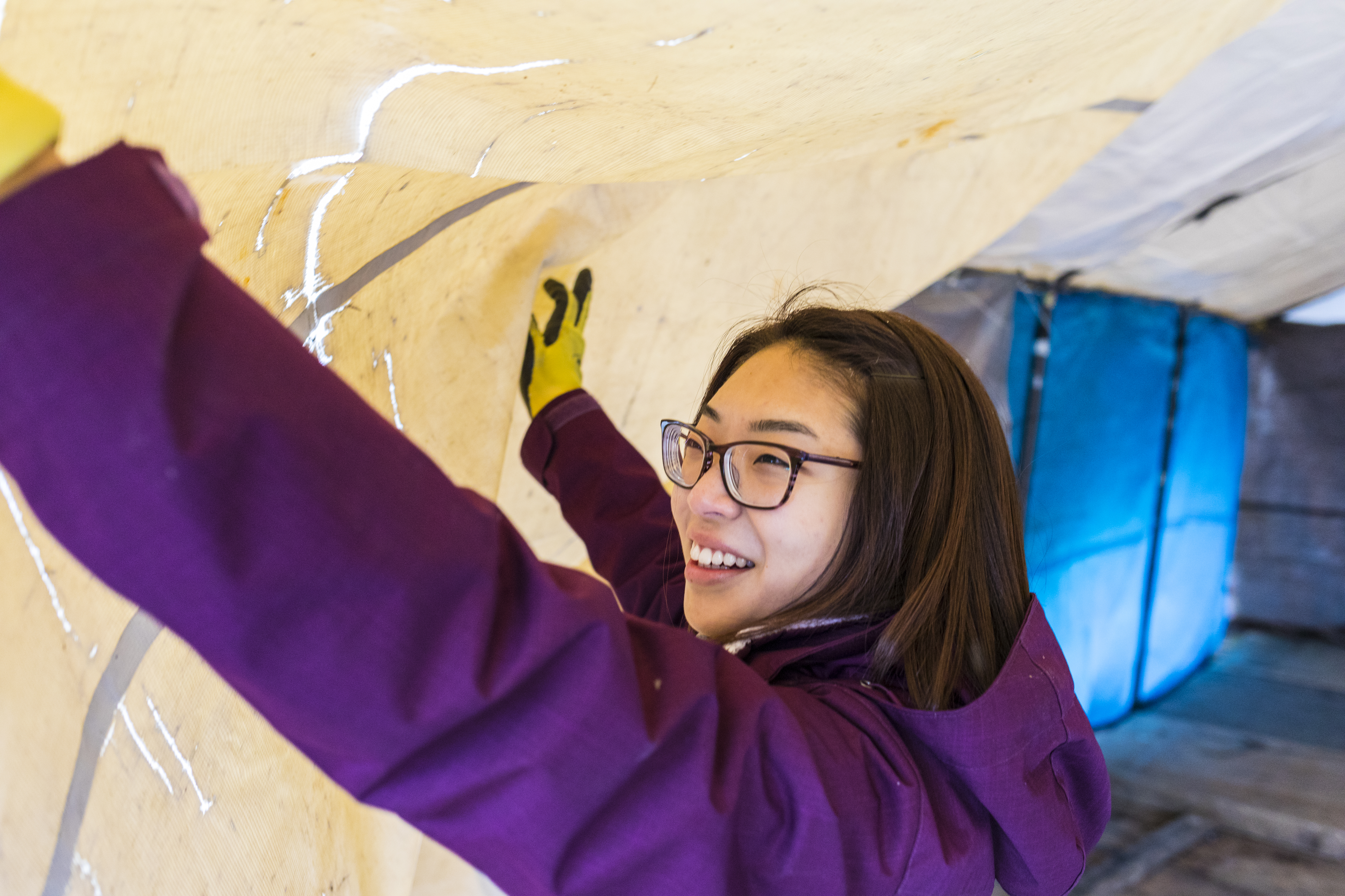 A student helps lift a tent during Tent City 3's December move-in day