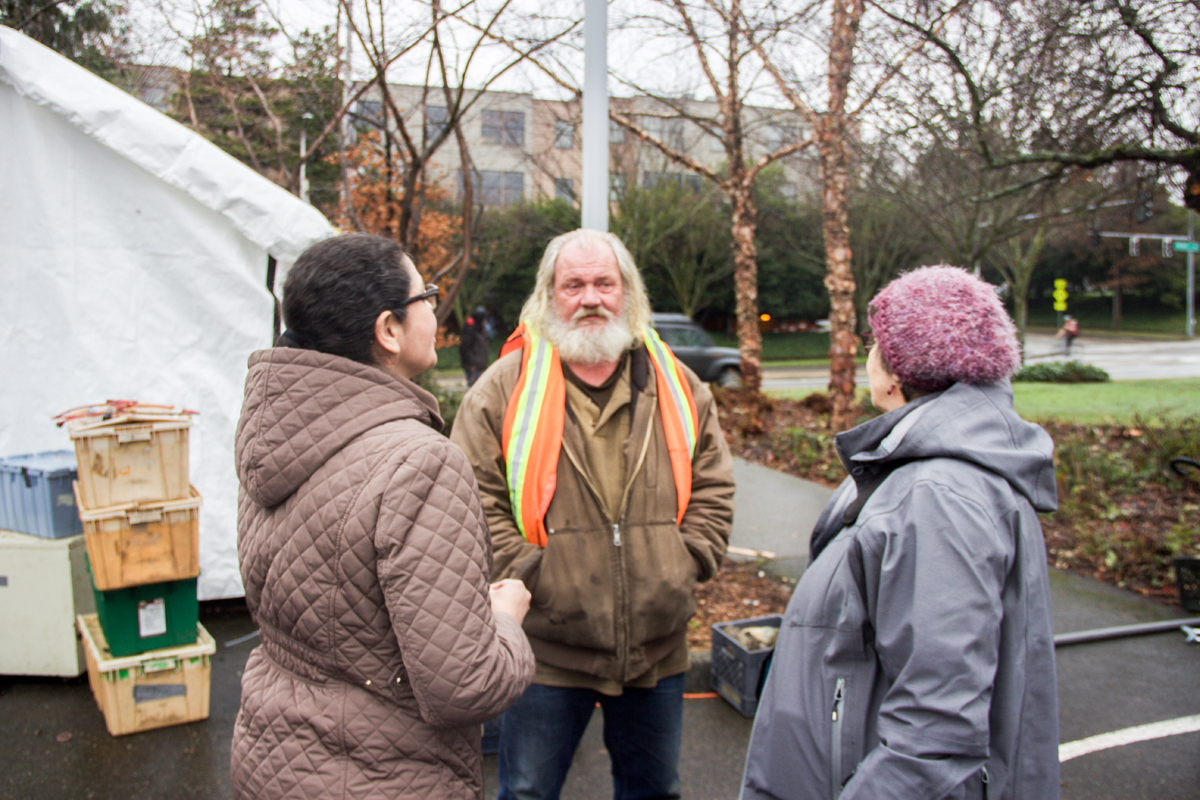 Charlotte Sanders, MSW, and Lois Thetford, PA-C, speak with Tent City 3 resident Art.