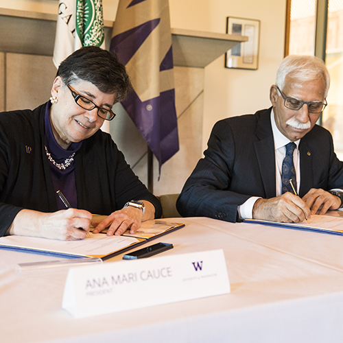 Image of UW President Cauce and AKU President Rasul signing the agreement