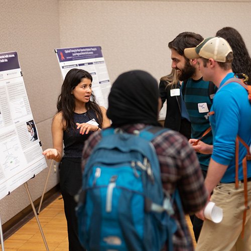 Image of student presenting research poster