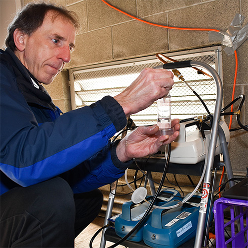 DEOHS Research Scientist Tim Gould checks air sampling instruments set up on the roof of the SeaTac Community Center.