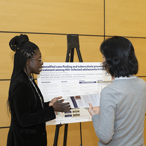 Image of student presenting their research poster