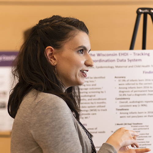 Image of student presenting her research poster