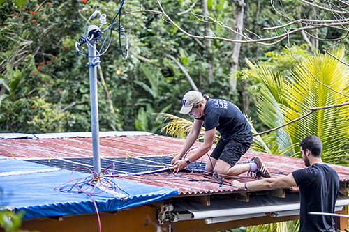UW faculty member and graduate student installing a solar panel on a storm-damaged roof