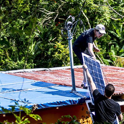 UW student handing a solar panel to a faculty member on the roof of a damaged home