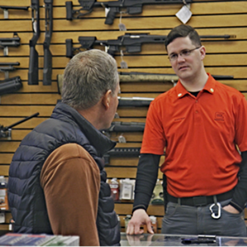 Brett Bass, a gun retailer and coordinator of Forefront Suicide Prevention's Safer Homes, Suicide Aware program, talks with a customer about firearm safety