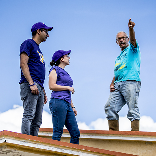 Image of two UW students talking to a man on the roof of a storm-damaged home